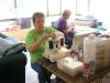 Kathy Qualls concentrates on threading her serger while Wanda Archer works on curtains for Glorieta.