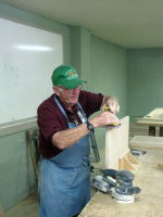 Much sanding is required prior to painting the items we make.  Coy Hearin uses a palm sander on this headboard piece.