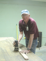 Leon Koenig uses a router to roundover the edges of a bunkbed headboard piece prior to assembly.