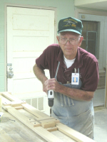 Richard Brewer is adding a cross to one of the bunk bed safety rails.