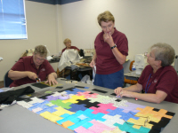 Ruth Reilly and Carol Temple work on the puzzle quilt.