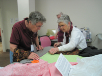 Ann Koenig and Kathryn Tennison cut strips for quilts.