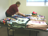 Ruth Reilly lays out some of the quilts for display.
