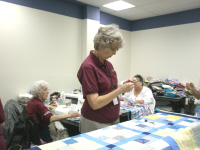 Doris Butler threads her needle to continue tieing her quilt.