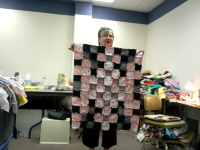 Peggy Steels' neighbor shows off her finished quilt.