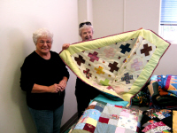 Sue Brewer shows a 'Hugs and Kisses' quilt to a friend.