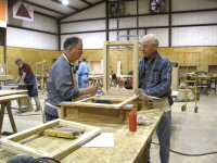 Eugene Esters, our most competent shop leader, shows Charles Oates how to assemble a dust cover for a desk.