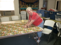 Barbara Cheatheam ties a quilt for Hanna House.