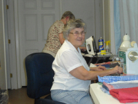 Peggy Steele works on clothes for a children's home.