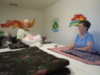 Another quilt ready for binding.  'Now, which of these can we use for backing on the next one' ponder Rita and Carolyn.