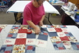 Kathy Qualls is laying out quilt pieces to get the best looking pattern.