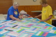 Freda Berry and Elaine Strong are making a last check on a quilt top before putting the top and bottom together..