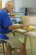 Guy Scott is sanding a cleat to use on an end rail.