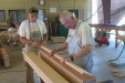 Harold Cheatheam and Guy Scott are preparing a stack of boards to glue together to make bed posts.
